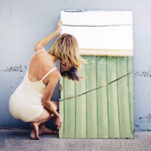 Rear View Of Woman Looking At Mirror Against Wall