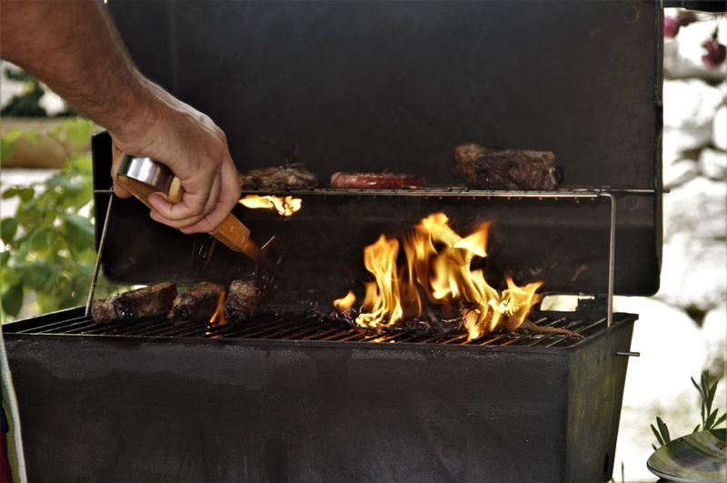Chicken Barbecue Barbecue Grill Burning Close-up Day Flame Food Freshness Grilled Heat - Temperature Human Body Part Human Hand One Person Outdoors Preparation  Preparing Food Real People Sausage