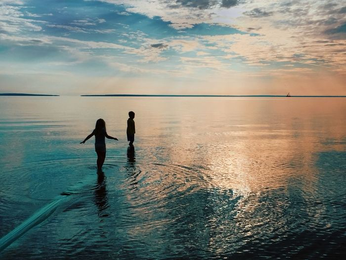 Silhouette girl and boy standing in sea against sky during sunset