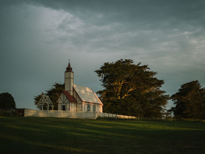 Low angle view of church by field against cloudy sky