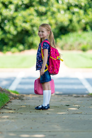 Side view portrait of schoolgirl with pink backpack standing on footpath