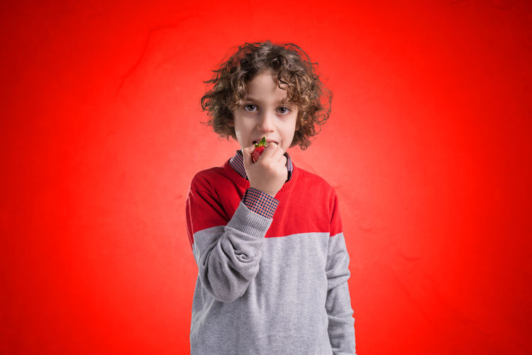 Cute kid eating a strawberry on a red background, studio shot. Concept kids eating fruits and healthy food. Red Backgrounds Childhood Studio Shot Child One Person Portrait Casual Clothing Hairstyle Innocence Looking At Camera Waist Up Holding Indoors  Front View Curly Hair 6 Years Old 7 Years Old Colored Background Offspring Standing Eating Food Strowberry Red Background Red Color Red Color 🎈 Vignetting Vignette Food And Drink Concept Eating Eating Strawberries  Strawberries Studio Photography Healthy Food Healty Fruit
