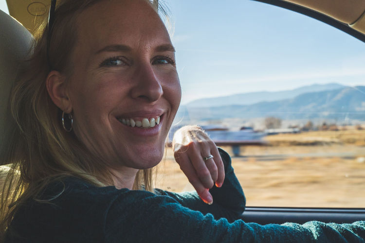 Smiling woman looks at camera while driving on road trip, view of desert out of drivers window