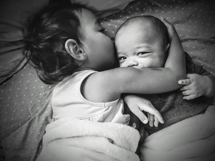 Cute girl with baby embracing on bed at home