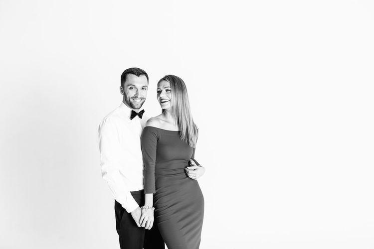 Happy elegant couple standing against white background