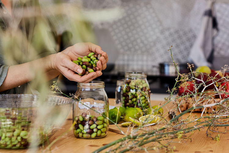 Midsection of person holding grapes on table