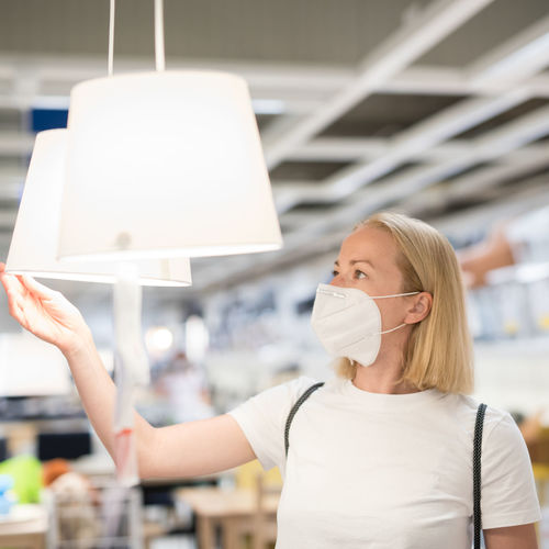 Close-up of woman wearing mask standing at store