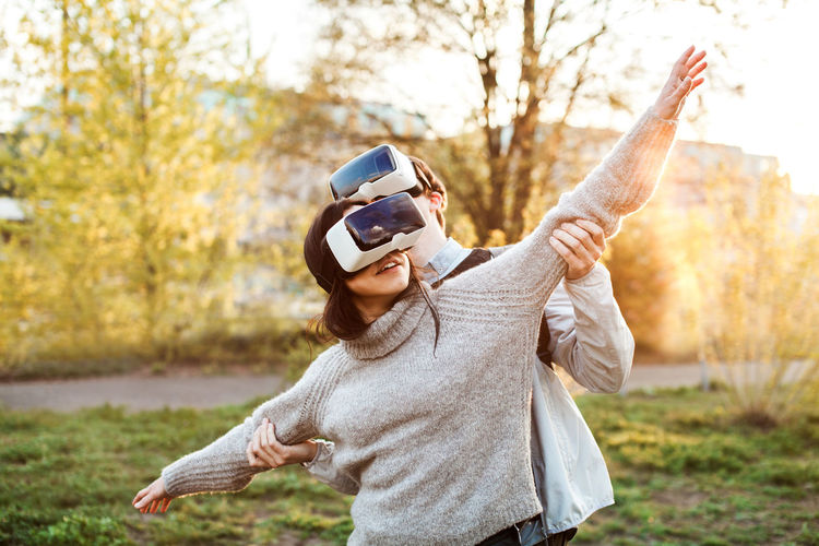 Couple of young adults playing with VR headsets Couple Friends Fun Grass Love Virtual Reality Friendship Headset Outdoors Park Playing Real People Summer Technology Vr