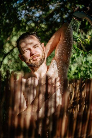 Shirtless man taking shower outdoors