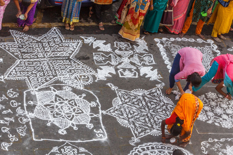 High angle view of females making rangoli on footpath during competition