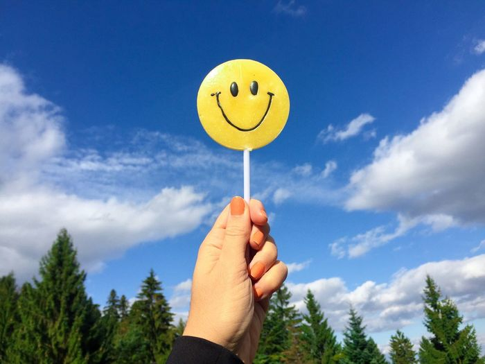 Close-Up Of Hand Holding Smiley Face Candy Against Blue Sky