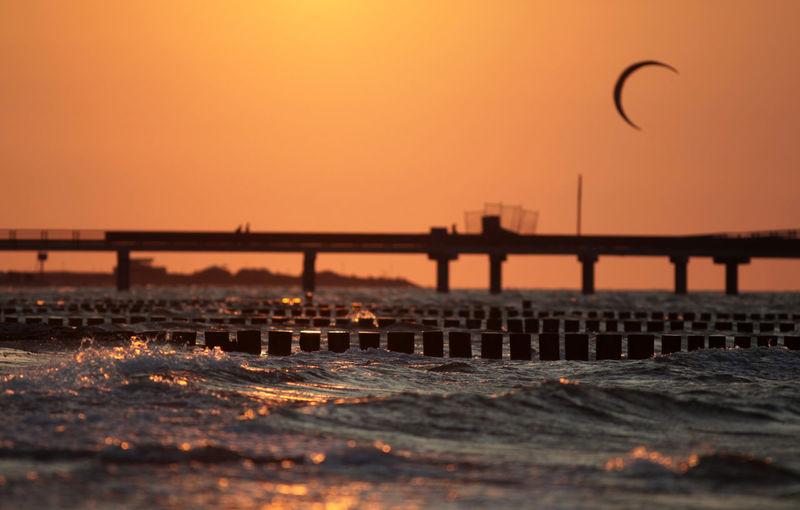 Surface level of sea against orange sky during sunset