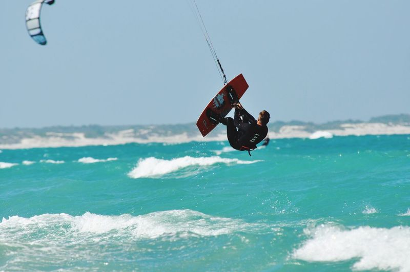Man kiteboarding over sea
