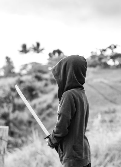 Portrait of a boy holding a wooden sword play. Casual Clothing Day Field Focus On Foreground Holding Hood - Clothing Land Leisure Activity Lifestyles Males  Men Nature One Person Outdoors Real People Side View Sky Standing Three Quarter Length Waist Up