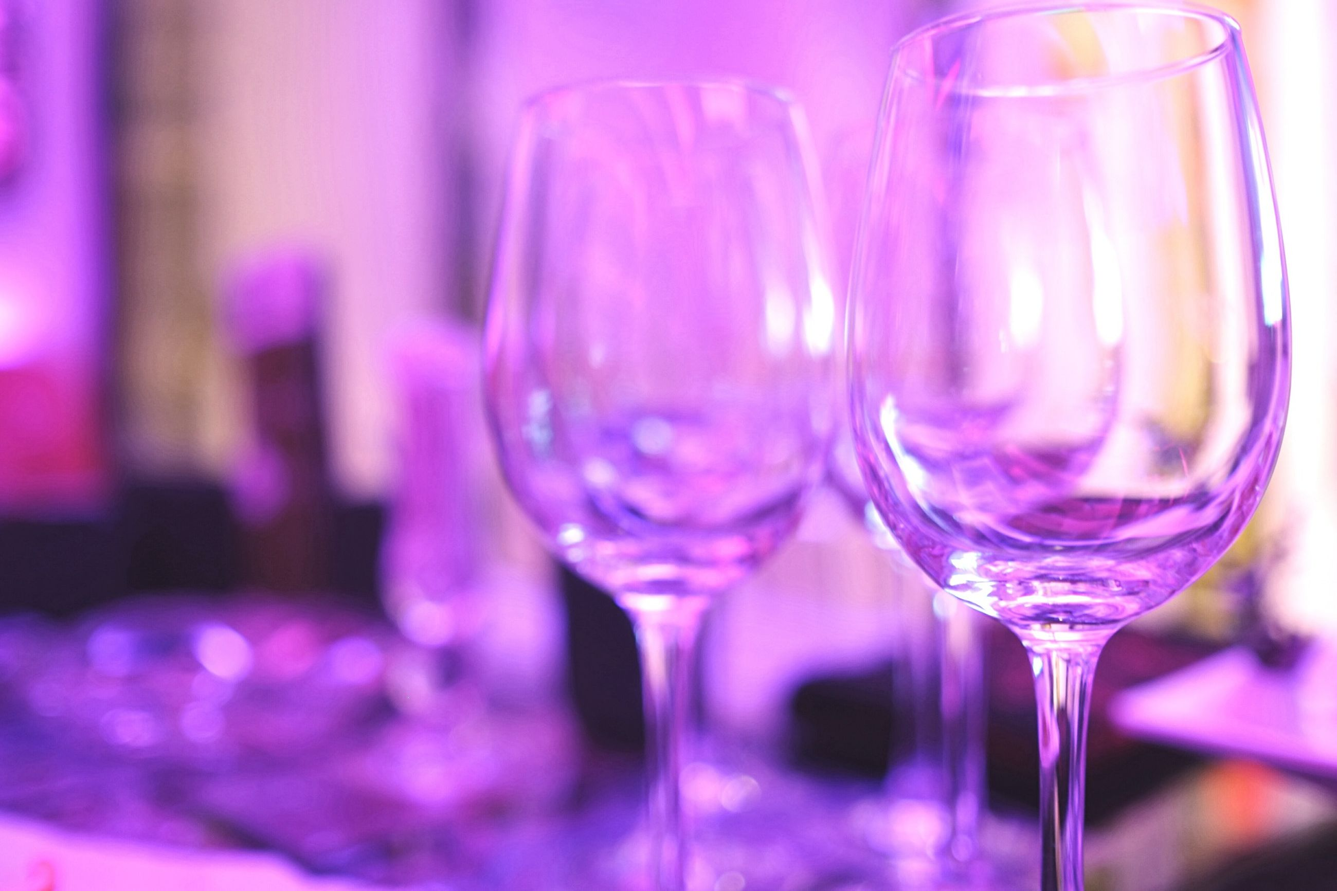 glass - material, transparent, indoors, drinking glass, freshness, drink, close-up, wineglass, refreshment, fragility, food and drink, focus on foreground, table, glass, still life, selective focus, flower, alcohol, wine, pink color