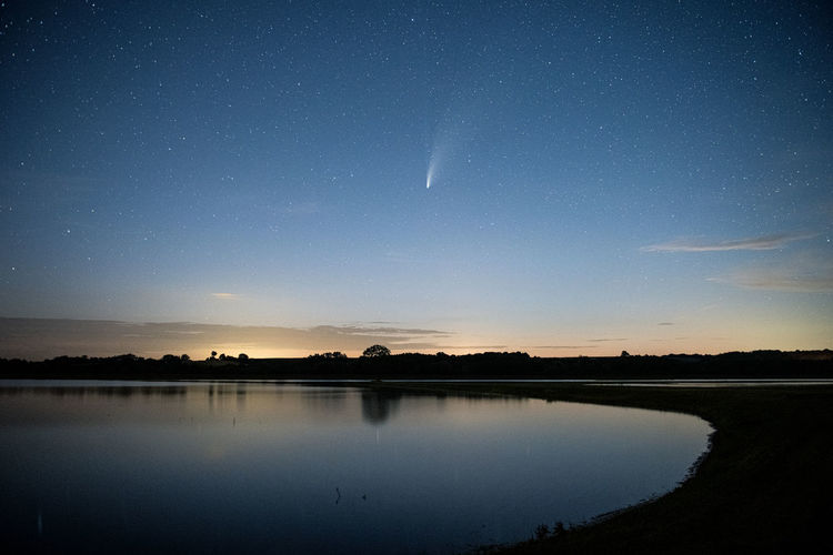 Scenic view of lake against sky at night neowise comet