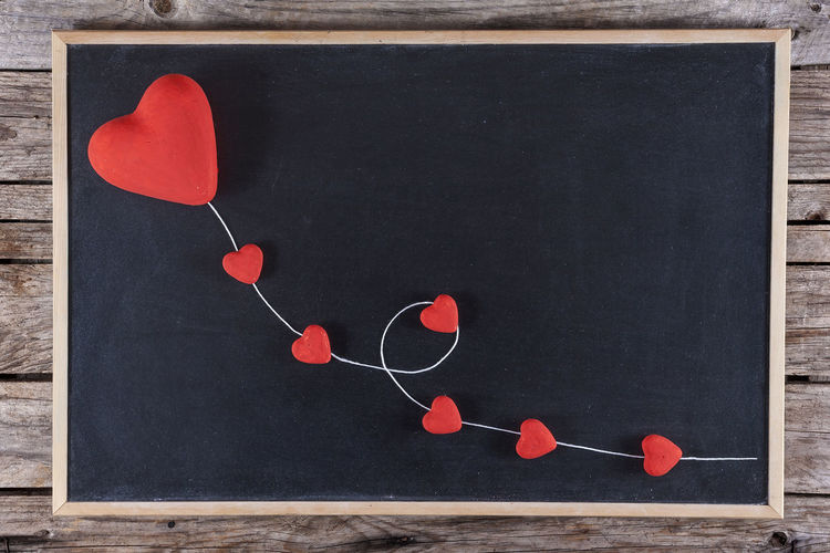 Red hearts kite on blackboard with wooden background Heart Shape Art And Craft Wood - Material Love Creativity Red Positive Emotion Table Still Life Emotion Indoors  No People Directly Above Design Craft Shape Thread Close-up High Angle View Paper Personal Accessory