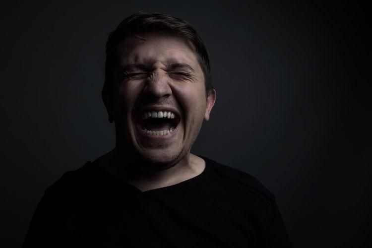 Man Screaming Against Black Background