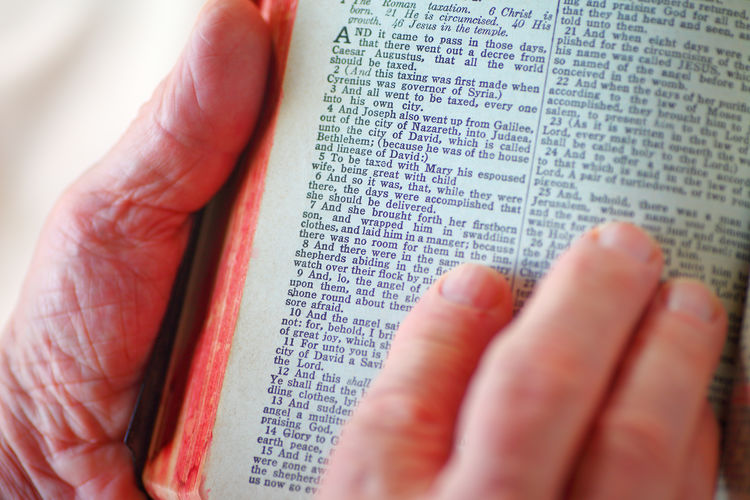 Man with hands on vintage Bible on Luke chapter Publication Text Book Hand Communication Holding Reading Paper One Person Close-up Belief Studying Holy Book Scriptures Religious  Spiritual Point Of View Man Christmas Story Christianity Fingers Natural Light Studio Shot
