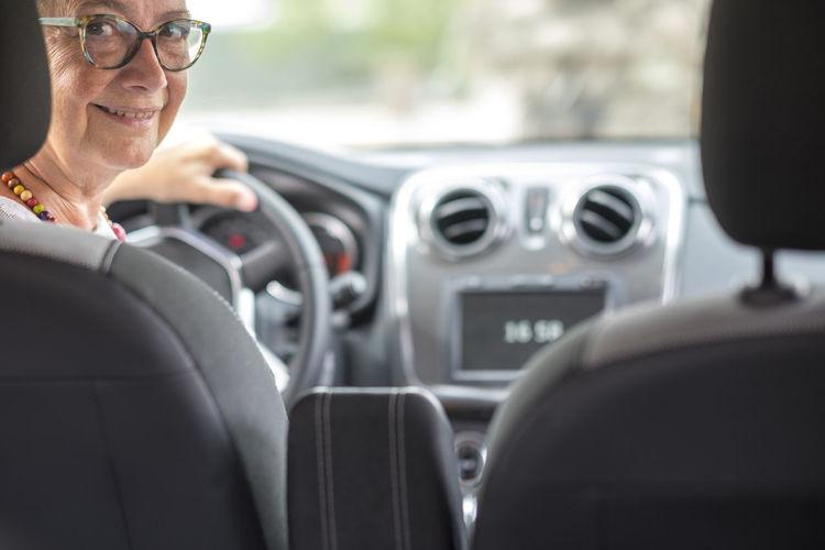 Portrait of smiling senior woman sitting in car