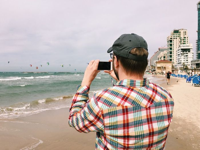 Rear view of man photographing at beach against sky