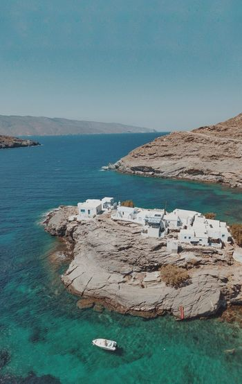 Drone photo of a secret place in tinos white traditional blue and white houses near the sea.