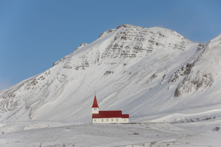 Built structure on snowcapped mountain against sky