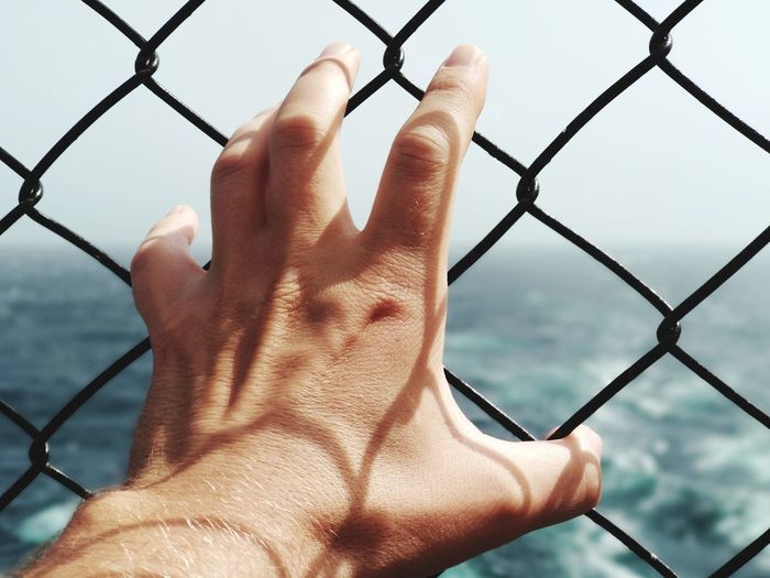 Where is freedom? Human Hand Water Sea Protection Nautical Vessel Safety Metal Getting Away From It All Chainlink Fence Security Chainlink Fence A New Beginning