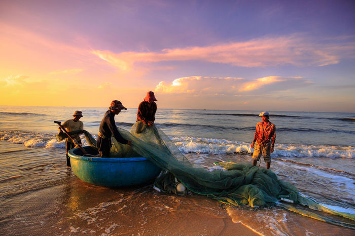 Fishermen who pull up the fishing nets when sunrise. This is ask for their daily work Basketball Agriculture Asian  Beach Boats Clouds And Sky Cloudy Colorful Sky Countryside Fishermen Fishery  Fishing Life Local Morning Ocean Outdoors Peasant Pull Up Seashore Tanned Village Waves Work Workdays