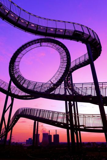 Low Angle View Of Rollercoaster Against Sky During Sunset