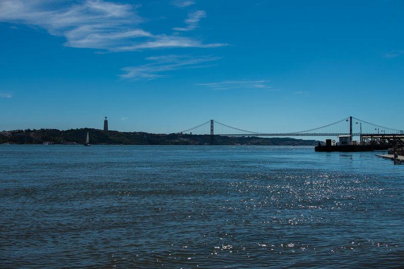 Distant view of april 25th bridge over tagus river against blue sky
