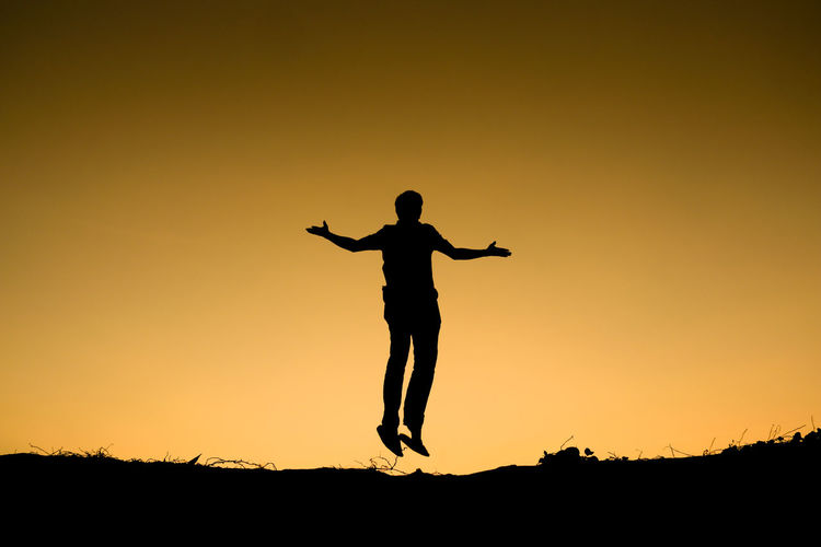Full length of silhouetted man jumping against sky during sunset