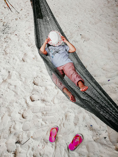 High angle view of woman lying in hammock at beach