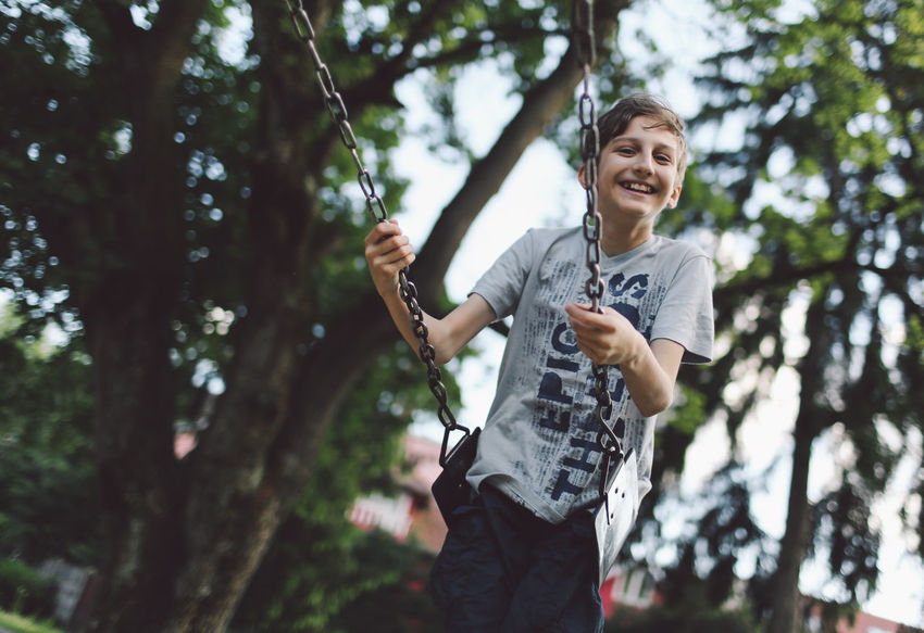 Boy Casual Clothing Child Children Confidence  Day Enjoyment Focus On Foreground Front View Fun Fun Happiness Leisure Activity Lifestyles Outdoors Person Playing Portrait Smiling Swing Swinging Toothy Smile Tree Young Adult
