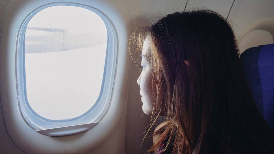 Close-up of woman looking through airplane window