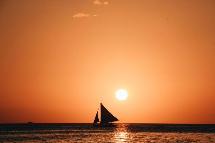 Silhouette boat sailing in sea