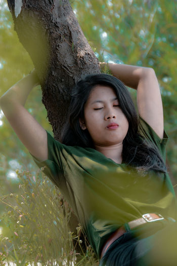 Young woman sleeping by tree