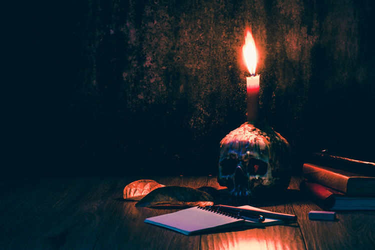 Illuminated Candle On Human Skull Over Table