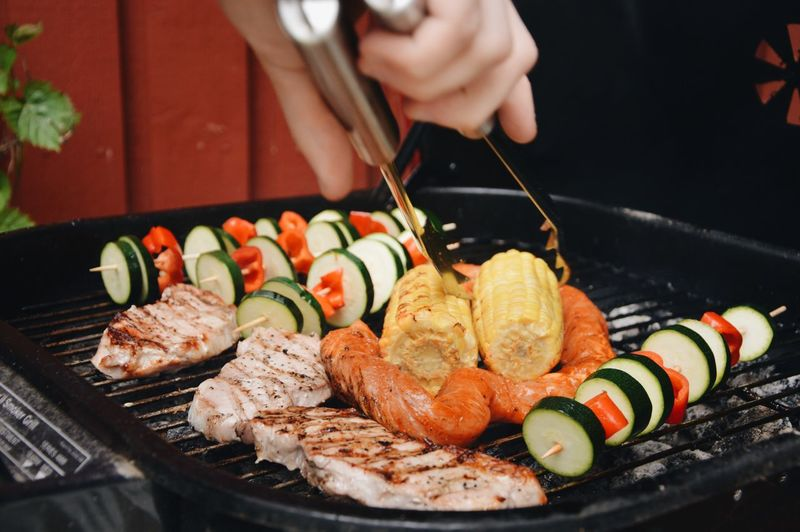 Hand of person preparing food on barbecue grill