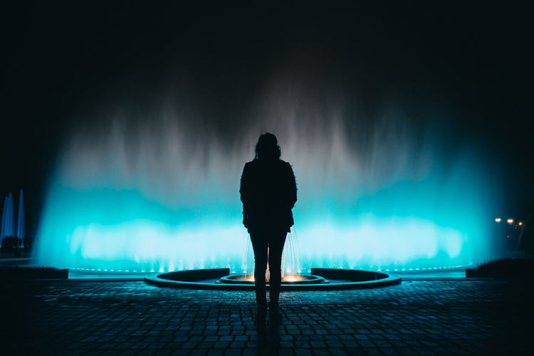 Rear view of silhouette woman standing by illuminated fountain at night