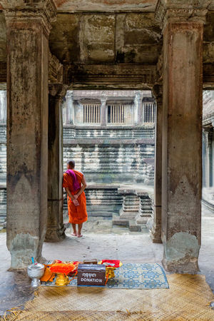 SIEM REAP - JUNE 11: An unidentified monk stands under an ornate arch in the main temple complex at Angkor Wat in Siem Reap, Cambodia on June 11, 2016. Angkor Thom Buddha Buddhist Cambodia Hindu Hinduism Khmer Culture Orange Tourist Tourist Attraction  Travel UNESCO World Heritage Site Angkor Wat Apsara Buddhism Cambodian Khmer Khmer Empire Khmer Temple Monk  Sculpture Southeast Asia Tourism Tourist Destination Unesco