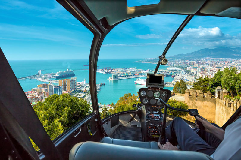 Helicopter cockpit flies in port of Malaga from the Gibralfaro Castle, Andalusia, Spain, with pilot arm and control board inside the cabin. Helicopter Flight Window Flying Plane Airplane Aerial View Panorama Console Interior Skyline Cityscape Cockpit Cockpit View Malaga Architecture Transportation City Building Exterior Built Structure Vehicle Interior Mode Of Transportation Sky Nature Water Day Sea Cloud - Sky Transparent Glass - Material Tree Outdoors Skyscraper