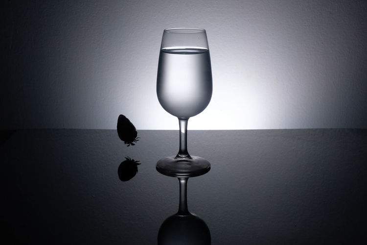 Close-up of wine glass on table against wall