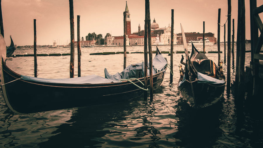Gondolas moored in grand canal by doges palace against sky