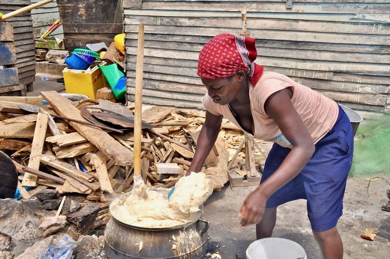 African African Cooking Faces Of Africa Ghana Woman Power Adult Africa Cooking Pot Fireplace Firewood Indigenous People Mash One Person Outdoor Kitchen Outdoors Preparation  Preparing Food Side View Slum Traditional Food Women Of The World Working
