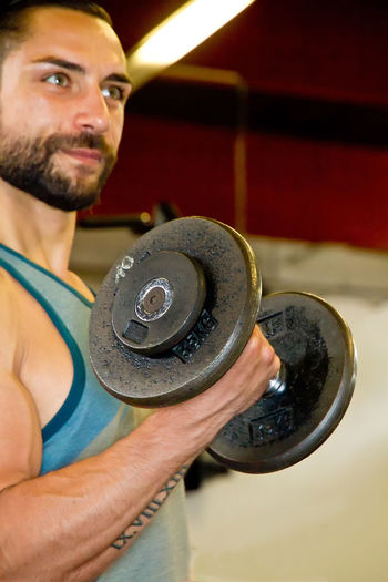 Young man training with dumbbell Adult Body & Fitness Happy Lifestyle Man Power Studio Young Arm Biceps Body Building Dumbbell Energetic Gym Handsome Health Healthy Holding Indoors  Lifestyles Muscles Muscular Build People Portrait Weight