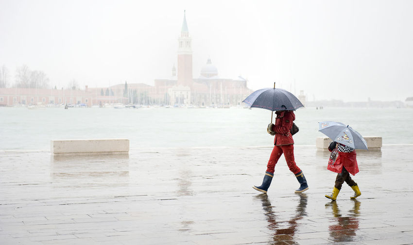 Man Walking With Child Against Grand Canal By Santa Maria Della Salute During Rainy Season