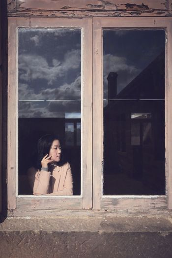 Thoughtful young woman standing by window seen through glass