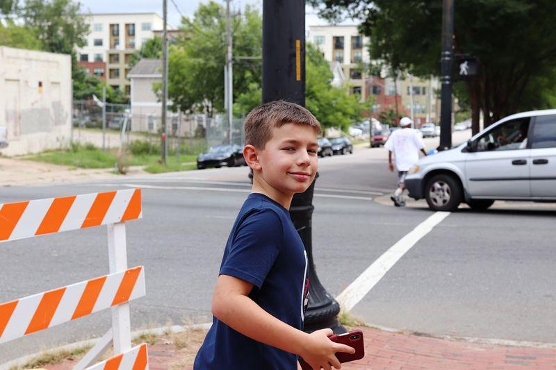 Portrait of boy on road in city