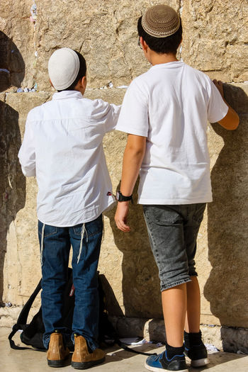 kids praying front the western wall Casual Clothing Clothing Couple - Relationship Day Full Length Hat Leisure Activity Lifestyles Love Males  Men Nature Outdoors People Positive Emotion Real People Rear View Sister Son Standing Sunlight Teenager Togetherness Two People Women
